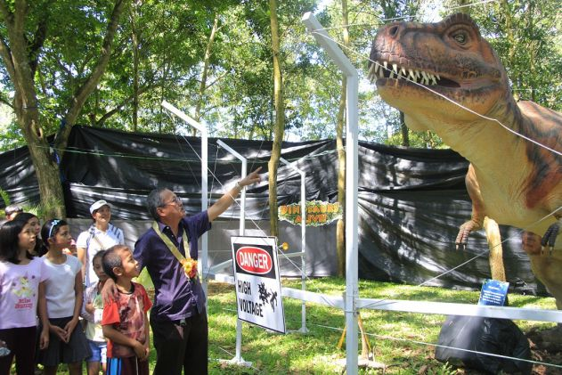City Administrator Rafael E. Abrenica introduces kids to one of the moving life-sized dinosaur replicas installed in the city's Energy Park. Photo by Louie Lapat of CIO Tagum