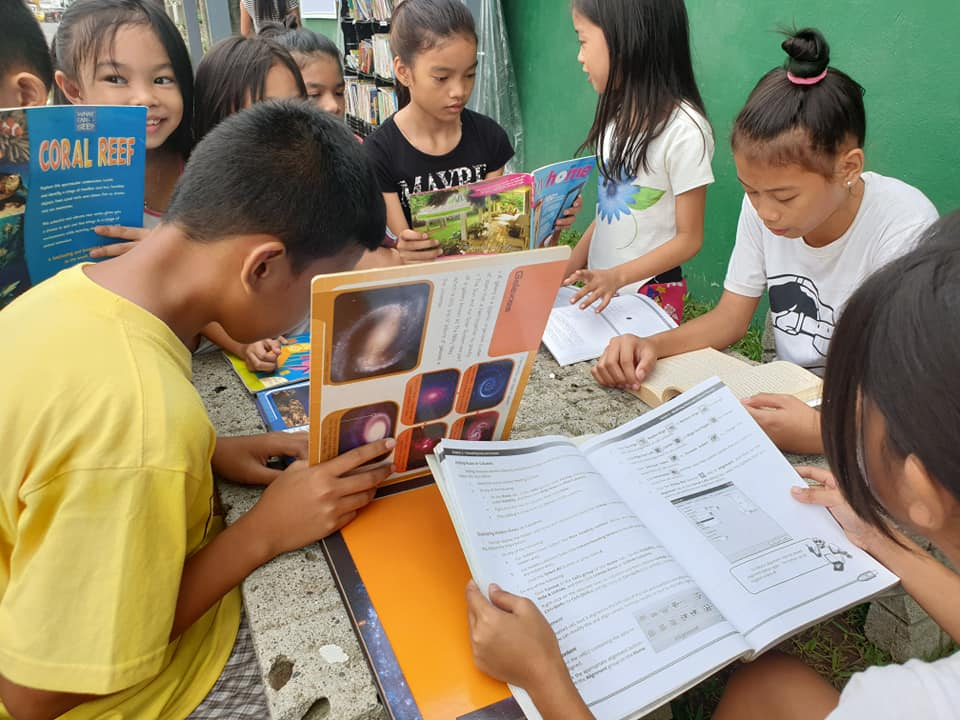 Children reading books at the Street Library in Davao